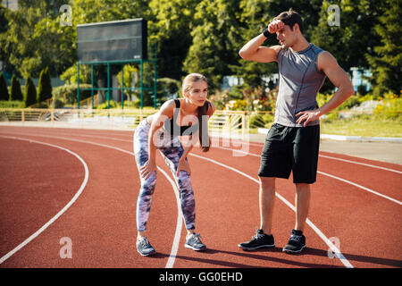 Tired fitness couple of runners sweating and taking a rest during marathon training at the stadium - Stock Photo
