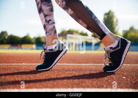 Close up portrait of a female runner feet running on stadium outdoors - Stock Photo