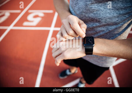Cropped image of a young muscular man standing on a treadmill at an open air stadium and adjusting smart watch - Stock Photo