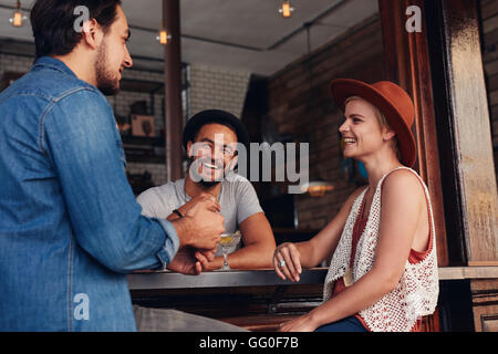 Young men and women sitting together and talking in a coffee shop. Group of young friends hanging out at a cafe. - Stock Photo