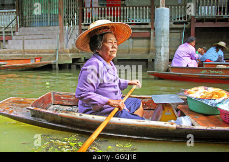 KANCHANABURI, THAILAND - JUNE 11, 2014: Unidentified woman is sails in the floating market along raft houses at - Stock Photo