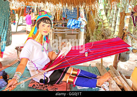 MAE HONG SON, THAILAND - JUNE 17, 2014: Unidentified Padaung (Karen) tribe woman weave on traditional device near - Stock Photo