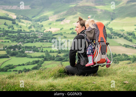 Young hiker with backpack child carrier and a baby girl inside, resting on the grass and looking at the beautiful - Stock Photo