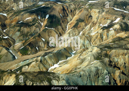 Aerial view of rhyolite mountains partially covered in snow, Landmannalaugar, Fjallabak Nature Reserve, Iceland - Stock Photo