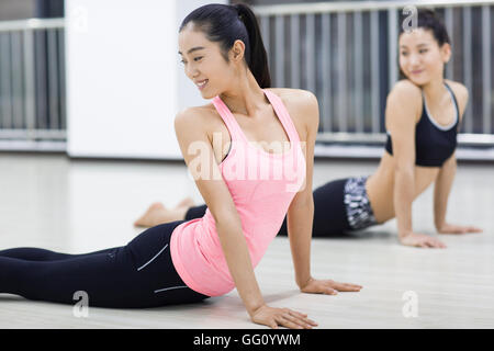 Young Chinese women practicing yoga at gym - Stock Photo
