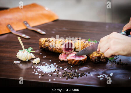 serving carving roast pork meat roll meal in rustic style with seasonings - Stock Photo