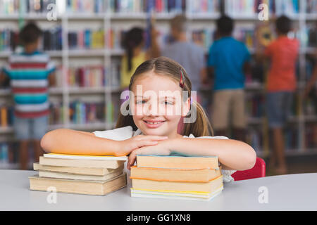 Smiling girl leaning on pile of books in library - Stock Photo