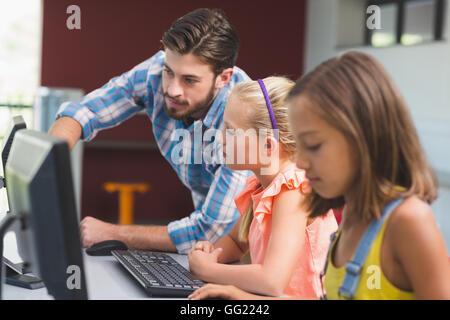 Teacher assisting schoolgirls in learning computer - Stock Photo
