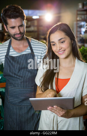 Male staff looking at digital tablet used by the woman - Stock Photo