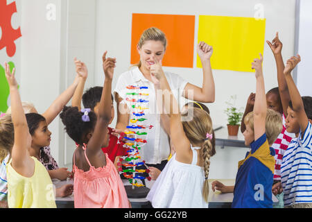 Teacher assisting kids in laboratory - Stock Photo