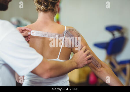 Male therapist measuring female patient back with goniometer - Stock Photo