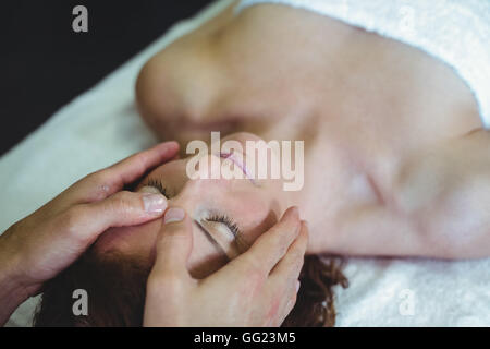 Woman receiving head massage from physiotherapist - Stock Photo