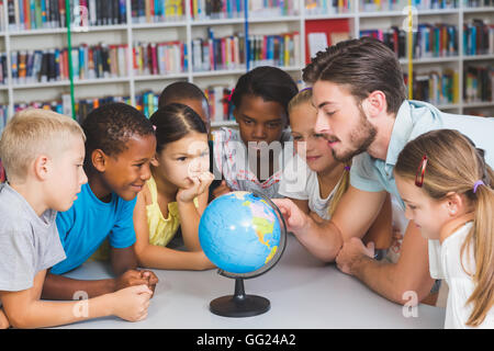 Pupils and teacher looking at globe in library - Stock Photo