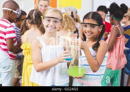 Portrait of kids holding laboratory flask in laboratory - Stock Photo
