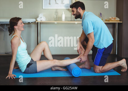Physiotherapist doing leg therapy to a woman using foam roll Stock Photo