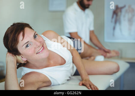 Woman receiving leg massage from physiotherapist - Stock Photo