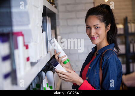 Smiling female hair dresser selecting shampoo from shelf at a salon - Stock Photo