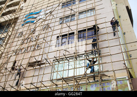 Chinese construction workers on bamboo scaffolding, Hong Kong, China - Stock Photo
