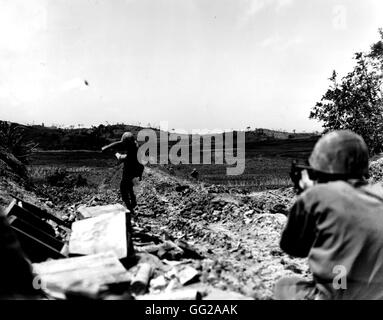 The Pacific War in Okinawa: American Marine throwing a grenade towards the Japanese lines May 6, 1945 Japan - World - Stock Photo