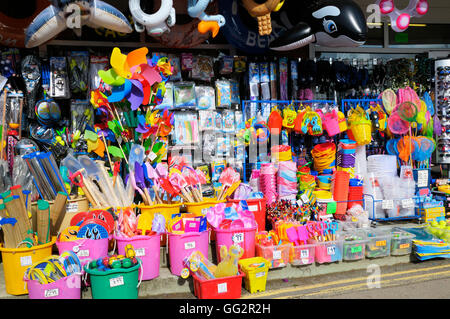 Colourful beach merchandise on sale outside a gift shop - Stock Photo