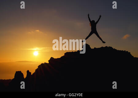 Young woman jumping at a sunset on a mountain of joy on holiday in the air - Stock Photo