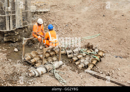 Construction workers sitting next to a pile drilling machine on a railway side site. In Ilkeston, Derbyshire, England. - Stock Photo