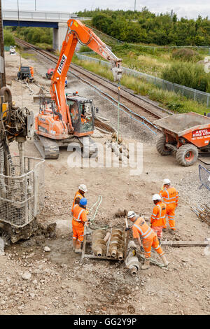 Construction workers moving helical pile drill screws on site next to a section of railway track. - Stock Photo