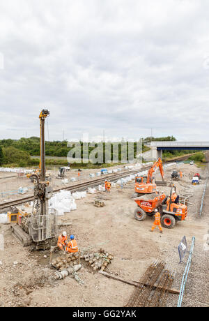 Construction workers on site next to a section of railway track. In Ilkeston, Derbyshire, England. - Stock Photo