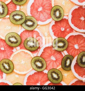 Fresh citrus fruits slices background viewed from above. Grapefruit, orange, kiwi pattern - Stock Photo
