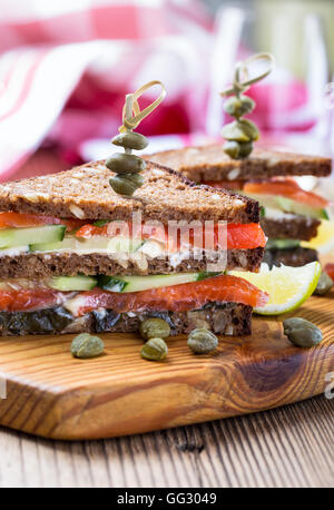 Homemade salmon club sandwich on rye bread with cucumber and sauteed spinach and secure with cocktail sticks - Stock Photo