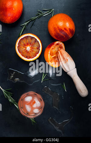 Fresh squeezed juice and blood oranges on gray background, top view - Stock Photo