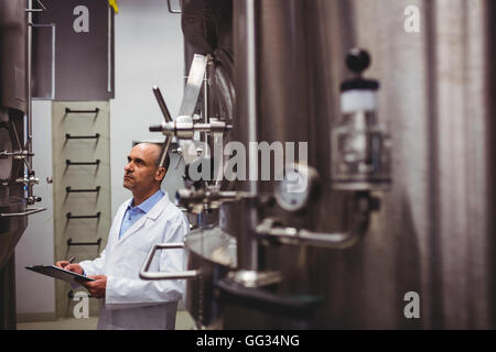 Manufacturer looking at storage tanks in brewery - Stock Photo