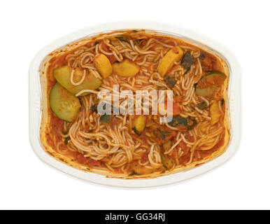 A cooked TV dinner of angel hair pasta with zucchini and spinach in a microwaveable tray on a white background. - Stock Photo