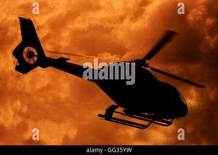 silhouette of helicopter taking off at sunset - Stock Photo