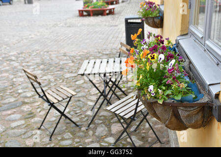 Lot of typical summer flowers in a basket under a window, picture from Sweden. - Stock Photo