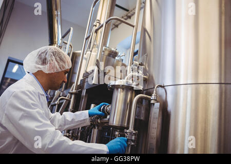 Manufacturer working at storage tanks in brewery - Stock Photo