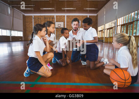 Sport teacher and school kids discussing on clipboard in basketball court - Stock Photo