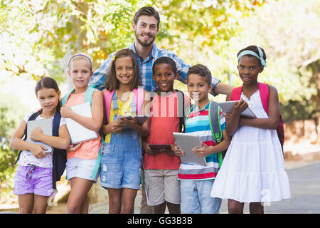 Teacher standing with school kids - Stock Photo