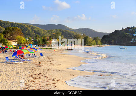 Golden sand, blue sky and colourful beach umbrellas at sunny Jolly Harbour, south-west Antigua - Stock Photo