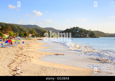Antiguan landscape and sightseeing: Golden sand, blue sky and colourful beach umbrellas at Jolly Harbour on a sunny - Stock Photo