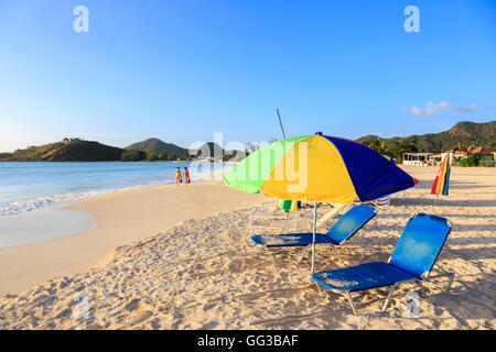 Sun parasol and loungers on golden sand beach at Jolly Harbour, south-west Antigua on a sunny day with blue sky - Stock Photo
