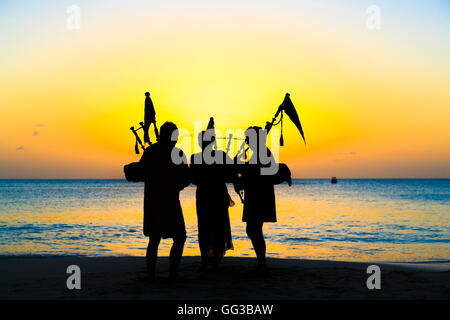 Bagpipers playing bagpipes on the beach at Jolly Harbour at sunset, south-west Antigua - Stock Photo