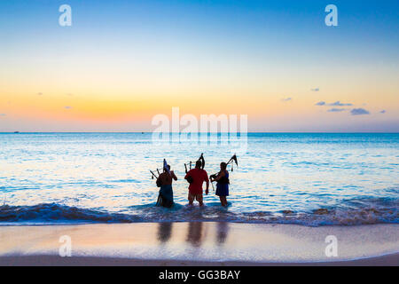 Bagpipers wading into the sea playing bagpipes on the beach at Jolly Harbour at sunset, south-west Antigua - Stock Photo