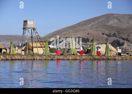 Floating reed village on Lake Titicaca, Peru, with Uros villagers - Stock Photo