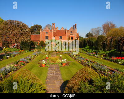 Chenies Manor House sunken garden with spring tulip borders, apple tree, ornamental pond, facing south west side - Stock Photo