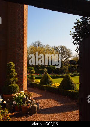 Portrait view of path through gate to Chenies Manor garden showing corner of the house with plant pots and topiary - Stock Photo