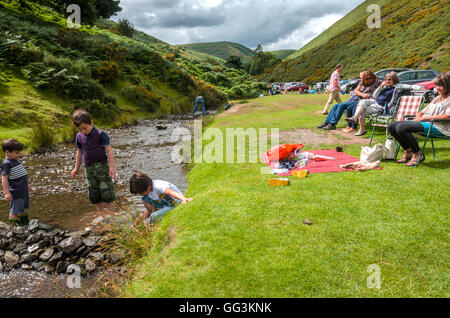A view down Carding Mill in Shropshire. Young children play in the stream. - Stock Photo