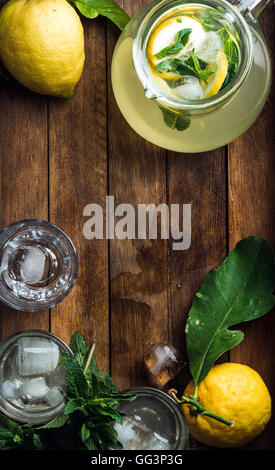 Jug with homemade lemonade, mint, fresh lemons and ice cubes on wooden background, top view, copy space - Stock Photo