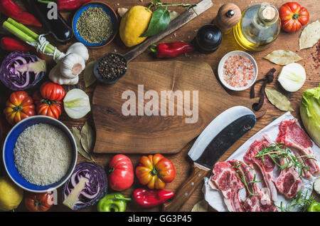 Raw uncooked lamb meat chops, rice, oil, spices and vegetables - Stock Photo