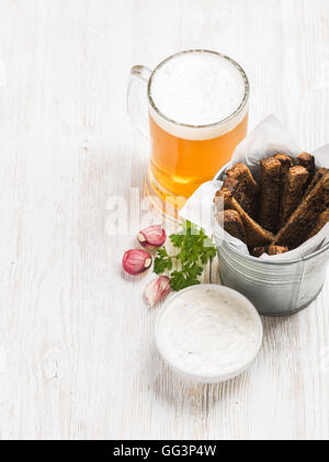 Beer snack set. Pint of pilsener in tall mug and rye bread croutons with garlic cream cheese sauce over white painted - Stock Photo